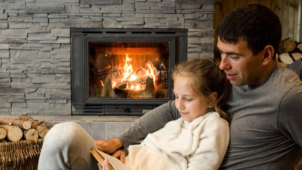 far og datter foran peisen