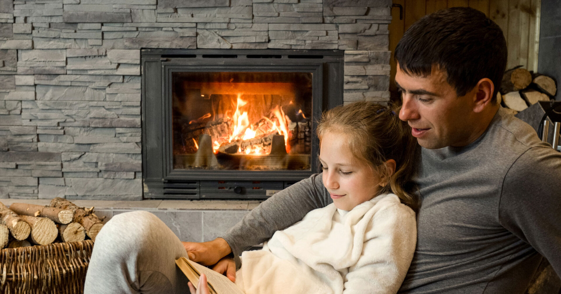 father and daughter in front of a fireplace