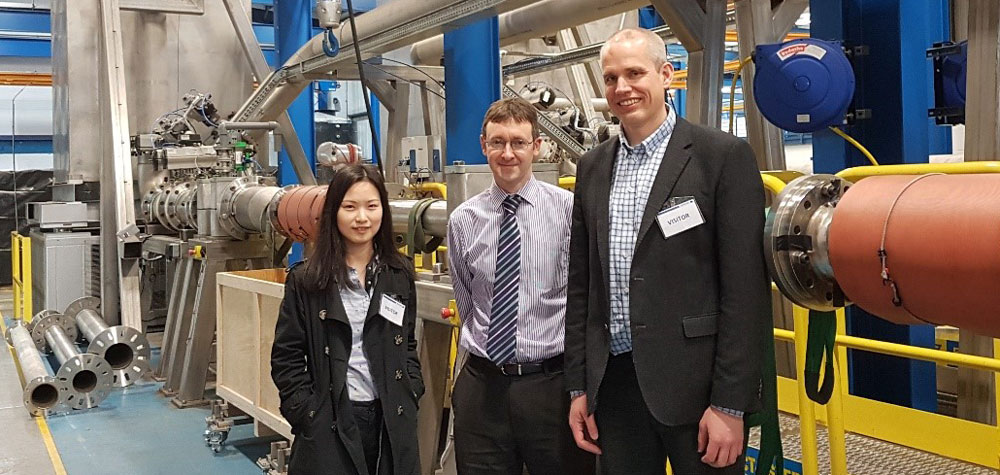 Research scientist Han Deng and Senior research scientist Sigurd W. Løvseth of SINTEF with Technical director Edward Jukes of KROHNE Ltd (middle) in front of the calibration facility. During calibration, tonnes of water are filled in the tank in the background. After a given time-period, the tank is weighed and the result compared with the reading of the flow meter under test.