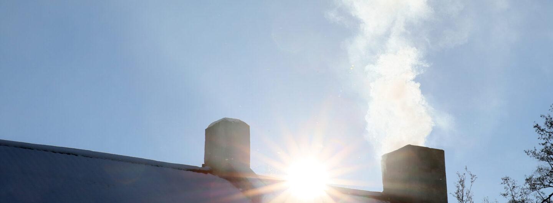 Hus med pipe og røyk. Sol i bakgrunn.