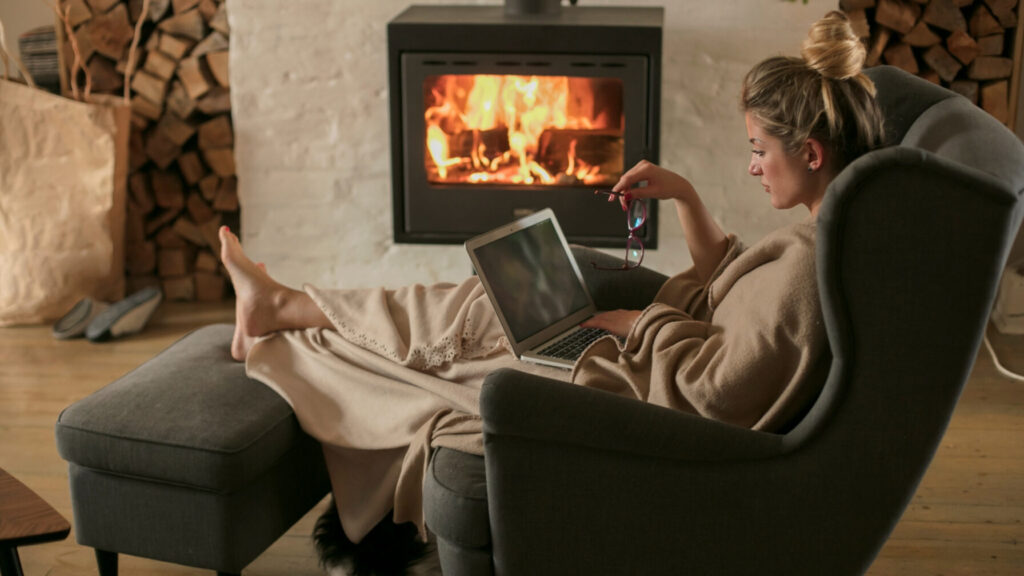 Woman working from home with a fireplace in the background