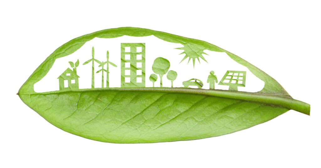 Green leaf cut in a way that shows a neighbourhood and various renewable energy sources