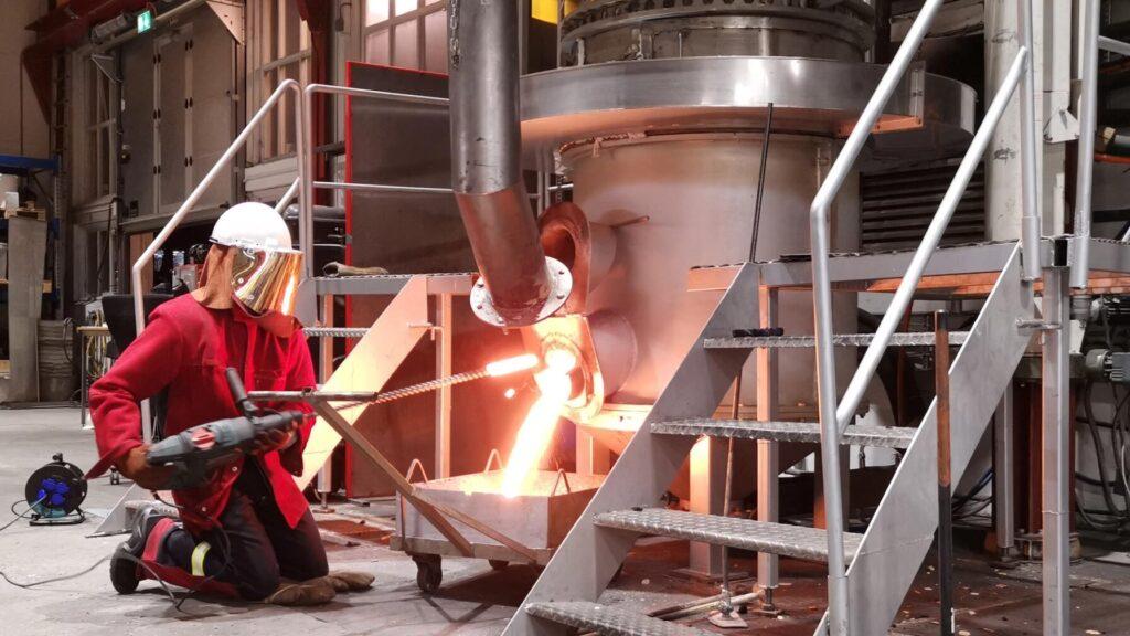 En operatør tapper flytende silisium fra en ovn